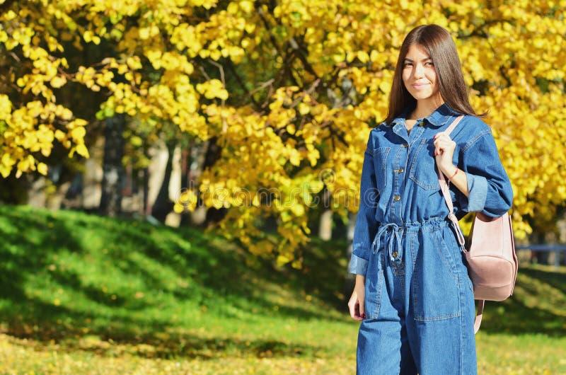 Caminar a la muchacha en parque del otoño Turista de la muchacha que mira alrededor en el parque en colores del otoño Chica joven foto de archivo libre de regalías