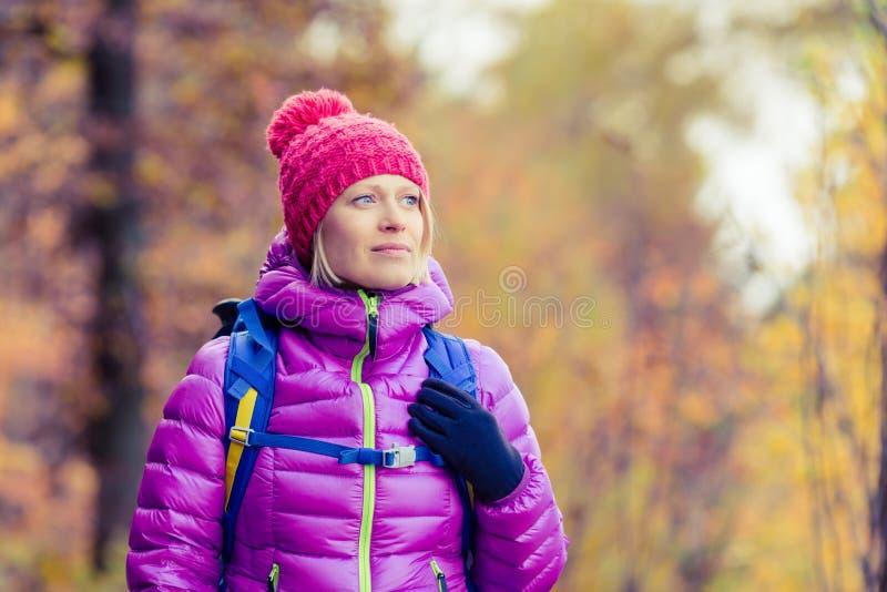 Caminar a la mujer con la mochila que mira la cámara en au inspirado fotografía de archivo