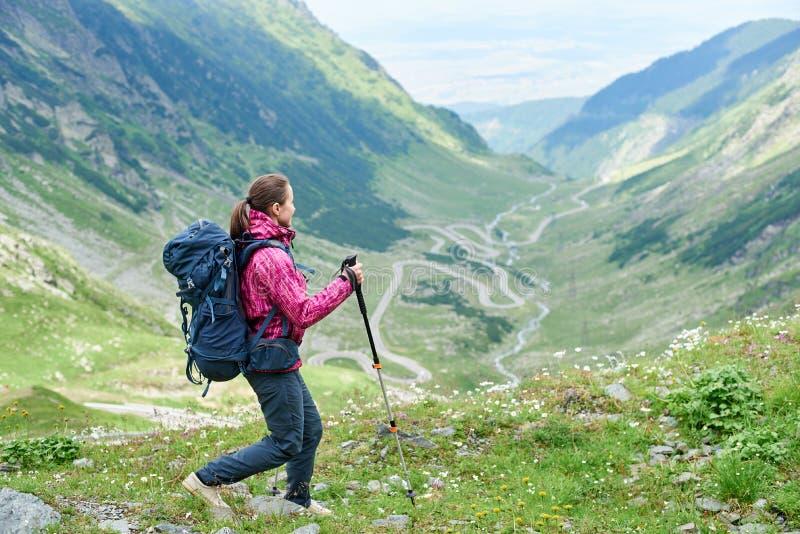 Caminar viaje en las montañas Rumania Muchacha con la mochila, emigrando los palillos foto de archivo libre de regalías