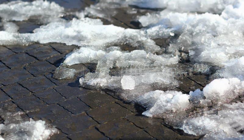 Camine en una nieve de fusión de la primavera en la acera foto de archivo
