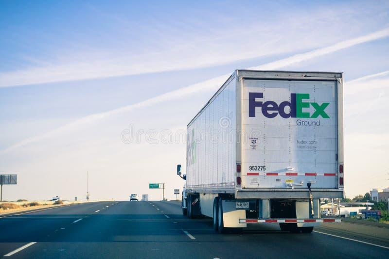 Caminhão à terra de Fedex que conduz na autoestrada em um ensolarado domingo de manhã imagens de stock royalty free