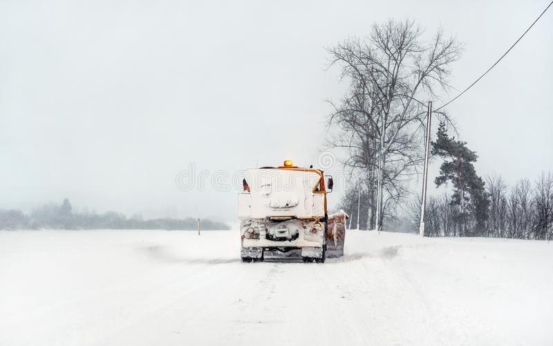 Caminhão alaranjado do arado na estrada coberto de neve, no céu cinzento e nas árvores no fundo - manutenção de estrada do invern imagens de stock