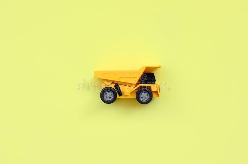 Caminhão amarelo pequeno do brinquedo no fundo da textura do papel amarelo pastel da cor da forma no conceito mínimo imagem de stock royalty free