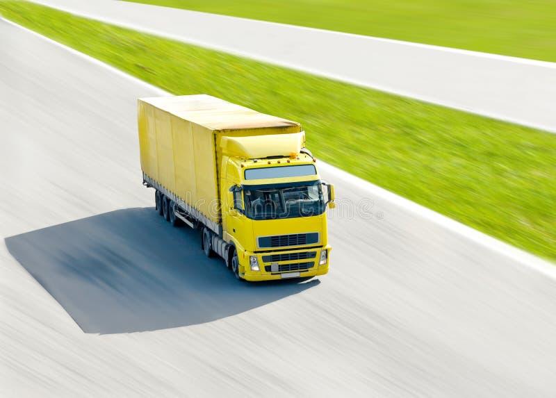 Caminhão amarelo vívido no movimento sob o sol brilhante foto de stock royalty free