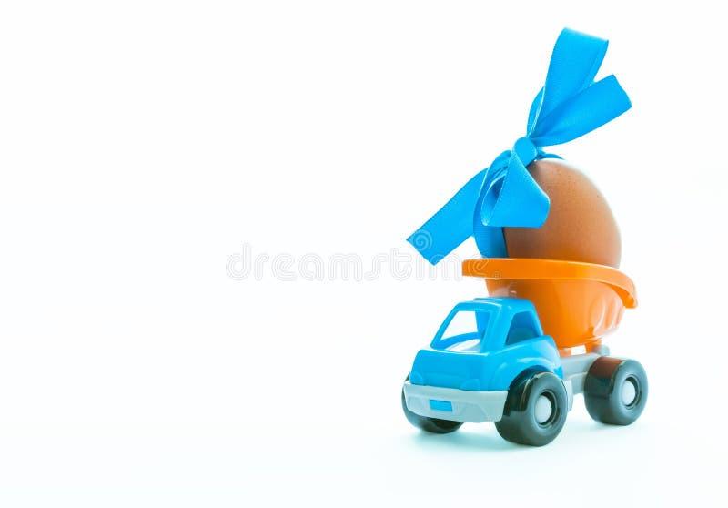 Caminhão automobilístico do ovo da páscoa e do brinquedo no fundo branco, conceito feliz do dia de easter, espaço para o texto fotografia de stock