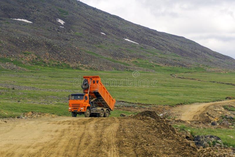 Caminhão basculante do caminhão basculante com um corpo em um estado levantado em uma estrada da montanha foto de stock royalty free