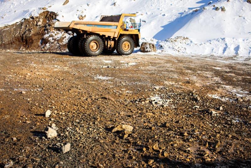 Caminhão basculante no fundo e pedras na estrada no foreg fotos de stock