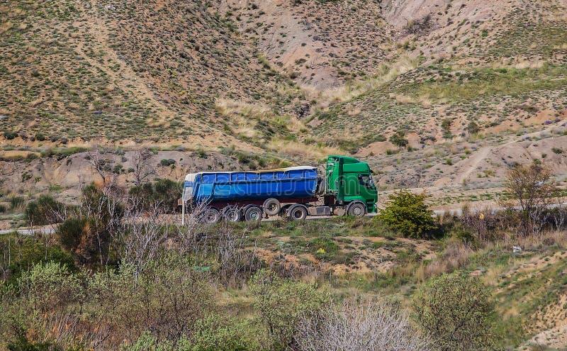 Caminhão basculante que move sobre uma estrada da montanha fotos de stock