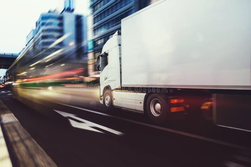 Caminhão branco que move-se rapidamente na estrada em uma cidade moderna com efeito da luz imagem de stock royalty free