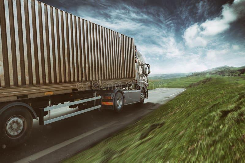 Caminhão cinzento que move-se rapidamente na estrada em uma paisagem natural com céu nebuloso imagem de stock royalty free