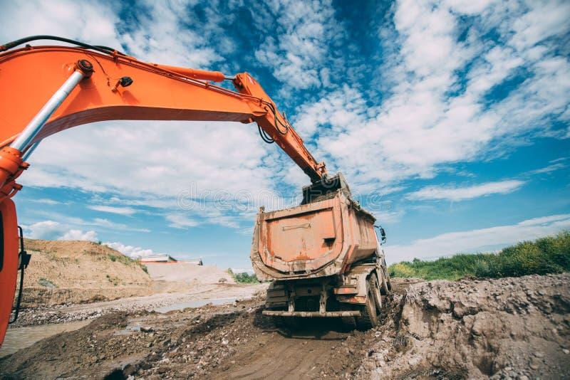 Caminhão de descarregador de trabalho da carga da máquina escavadora durante terraplenagens, canteiro de obras da estrada e trans imagens de stock