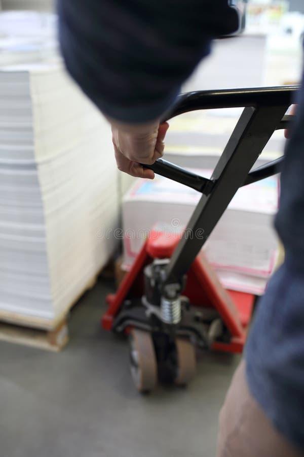 Caminhão de paletes, o trabalhador carrega as paletes no carrinho fotografia de stock