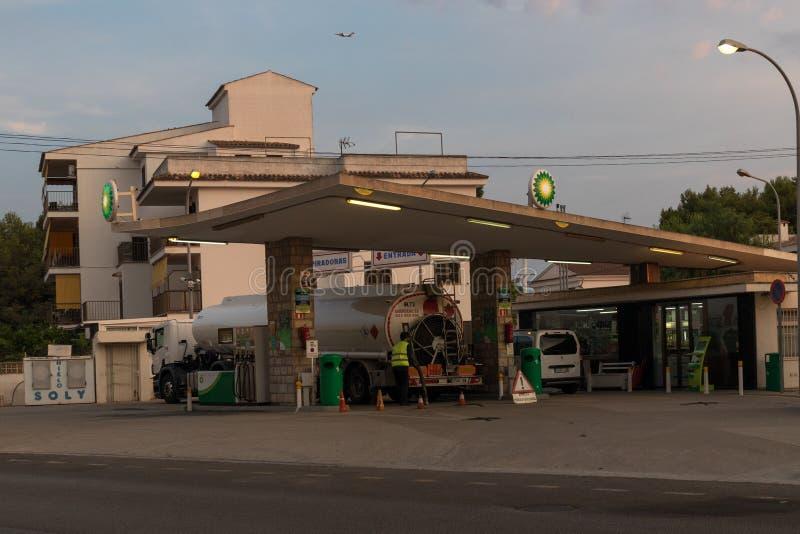 Caminhão de petroleiro que enche-se acima do tanque de armazenamento na estação do combustível cedo na manhã imagem de stock