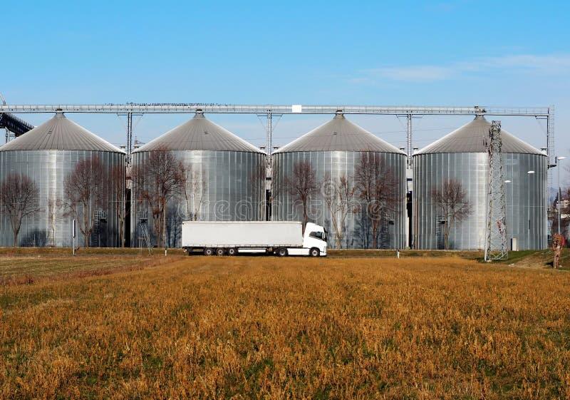 Caminhão de reboque longo branco do veículo na frente dos escaninhos de armazenamento da grão fotos de stock