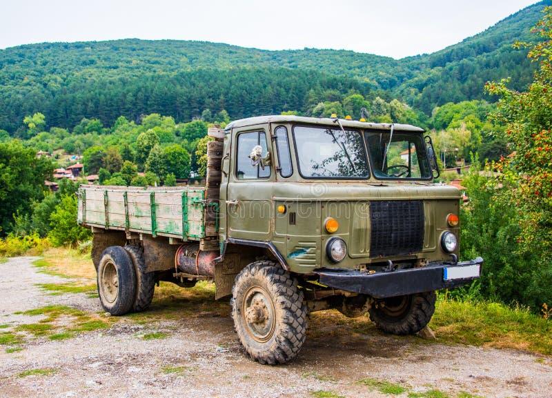 Caminhão de reboque na grama na frente do montanhas fotos de stock