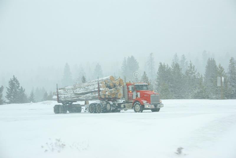 Caminhão de registo na estrada gelada foto de stock