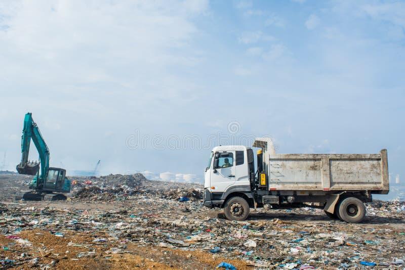 Caminhão e escavadora na descarga de lixo completamente do fumo, da maca, de garrafas plásticas, de desperdícios e de lixo na ilh fotografia de stock