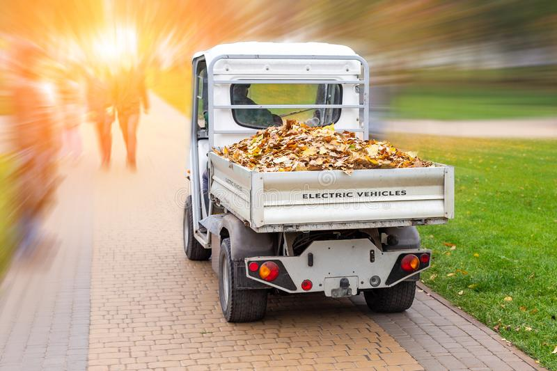Caminhão elétrico pequeno que remove as folhas caídas no corpo no parque da cidade do outono Serviços urbanos municipais usando o fotos de stock royalty free