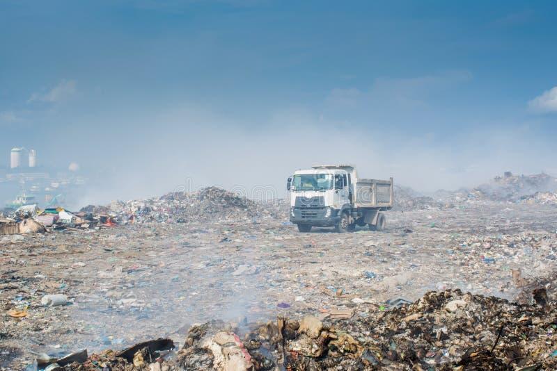 Caminhão na descarga de lixo completamente do fumo, da maca, de garrafas plásticas, de desperdícios e de lixo na ilha tropical imagem de stock