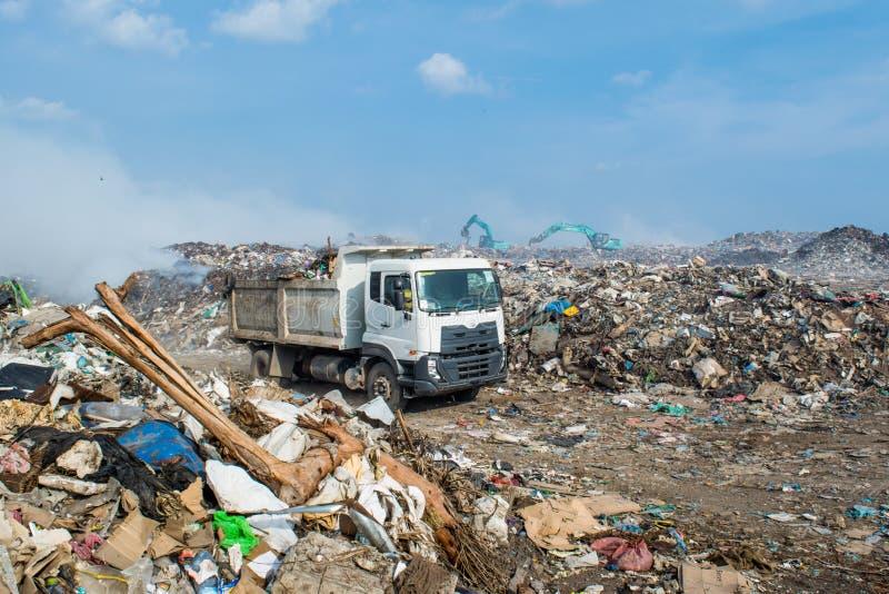 Caminhão na descarga de lixo enorme completamente do fumo, da maca, de garrafas plásticas, de desperdícios e de lixo na ilha trop fotografia de stock royalty free