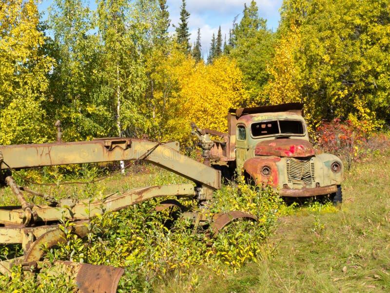 Caminhão oxidado e graduador esquecidos na floresta da queda fotografia de stock