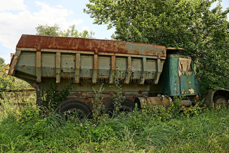 Caminhão oxidado velho que está na grama verde e na vegetação fotografia de stock