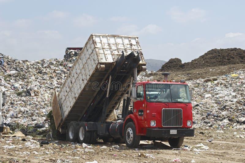 Caminhão que descarrega o lixo no local fotografia de stock royalty free
