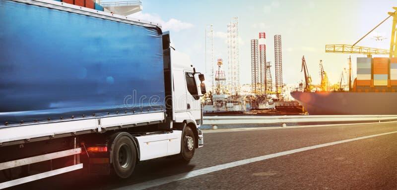 Caminhão que viaja rapidamente a um porto comercial no por do sol imagem de stock royalty free