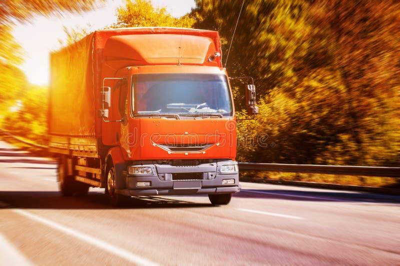 Caminhão vermelho na estrada asfaltada obscura imagens de stock royalty free