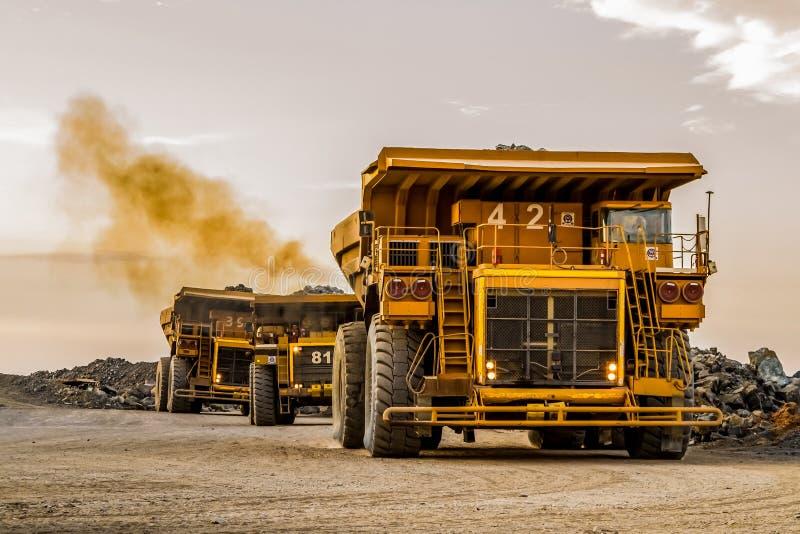 Caminhões basculantes da mineração que transportam o minério da platina para processar fotografia de stock royalty free