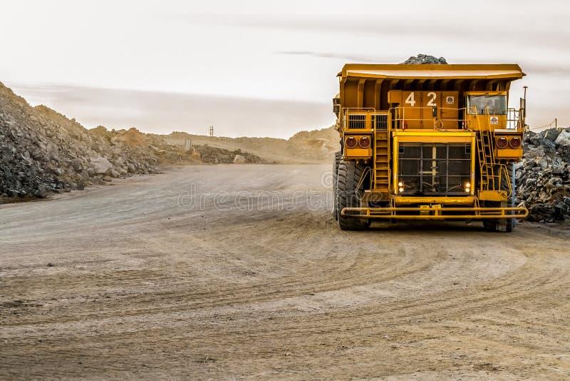 Caminhões basculantes da mineração que transportam o minério da platina para processar foto de stock