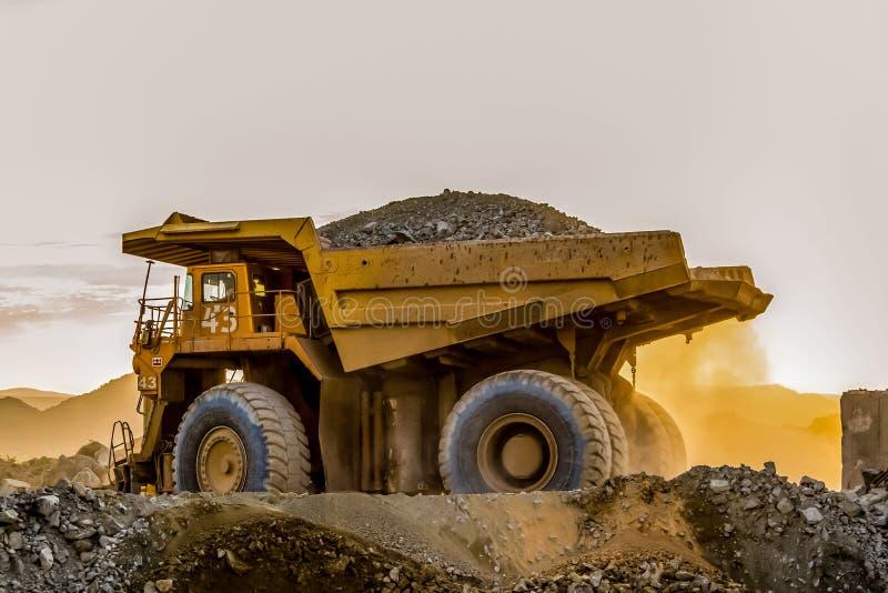 Caminhões basculantes da mineração que transportam o minério da platina para processar imagem de stock