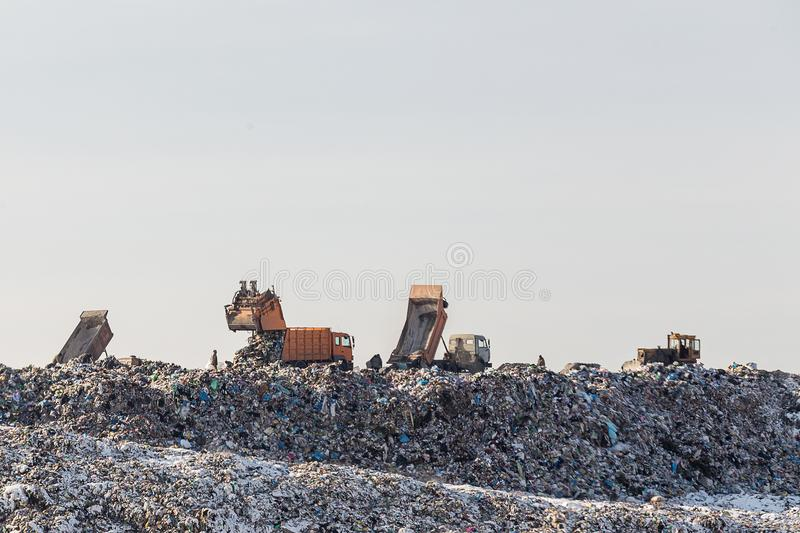Caminhões basculantes que descarregam o lixo sobre a operação de descarga vasta Poluição ambiental Método antiquado da eliminação fotos de stock