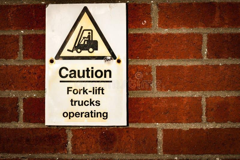 Caminhões de empilhadeira que operam o sinal de aviso fotografia de stock royalty free
