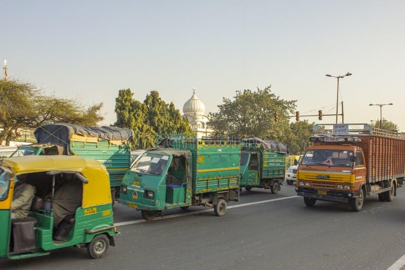 Caminhões verdes indianos do moto no tráfego de cidade em um fundo de árvores verdes e na abóbada de um templo branco fotos de stock royalty free