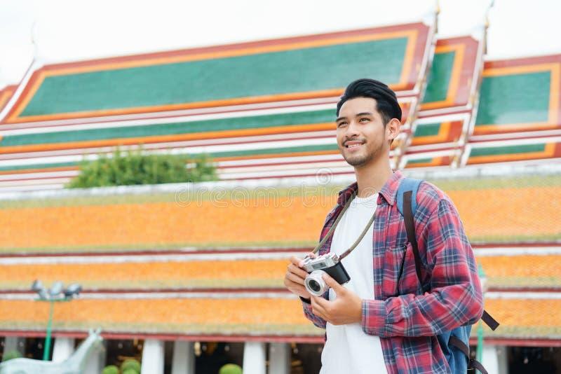 Caminhada asiática do turista do homem que toma a foto com a câmera do filme em Wat Suthat Thepwararam Ratchaworawihan Bangkok, T fotos de stock royalty free