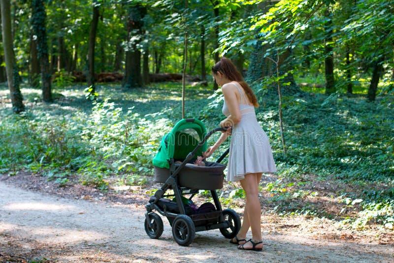 Caminhada com carrinho de criança, opinião lateral da floresta a mamã nova no vestido bonito que anda no caminho com seu infante  imagem de stock royalty free