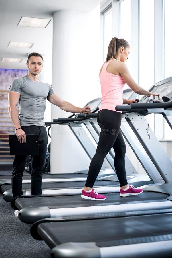 Caminhada da escada rolante com instrutor pessoal imagem de stock royalty free