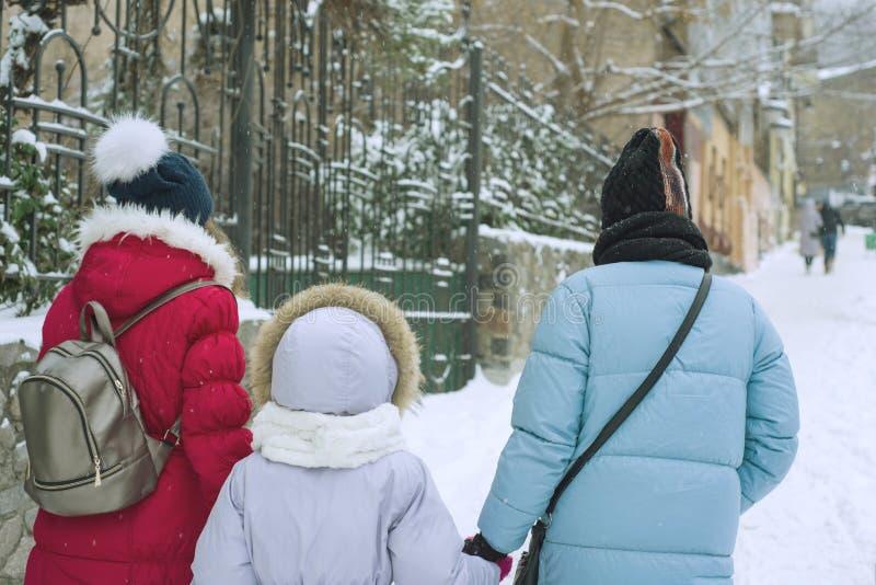 A caminhada da família do inverno na cidade, a mãe e suas filhas andam ao longo da rua coberto de neve da cidade, a vista da part fotos de stock royalty free