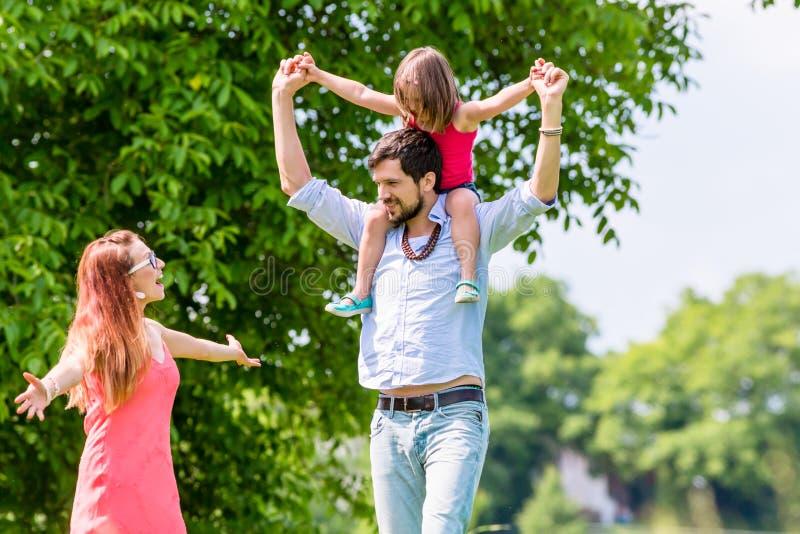 Caminhada da família - gene a criança levando em seu ombro fotos de stock royalty free