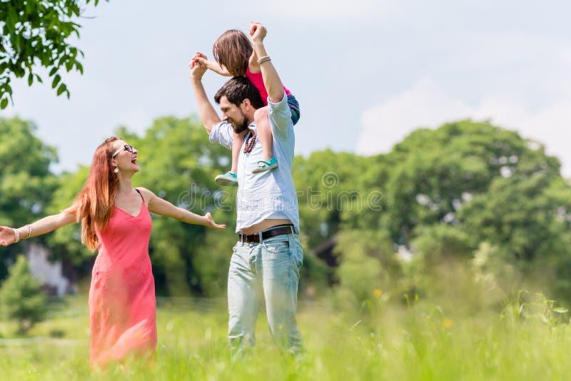 Caminhada da família - gene a criança levando em seu ombro foto de stock
