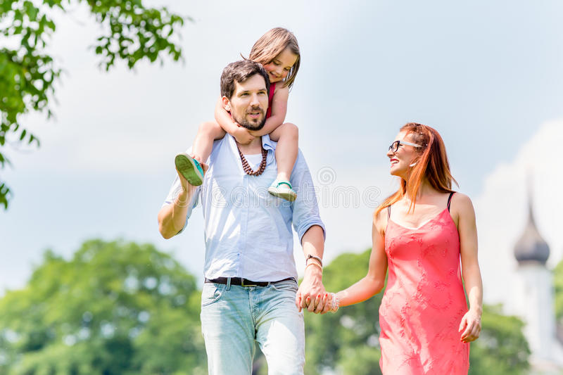 Caminhada da família - gene a criança levando em seu ombro foto de stock royalty free