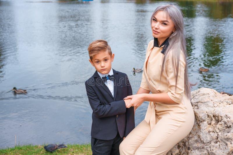Caminhada da m?e e do filho no parque pelo lago imagens de stock