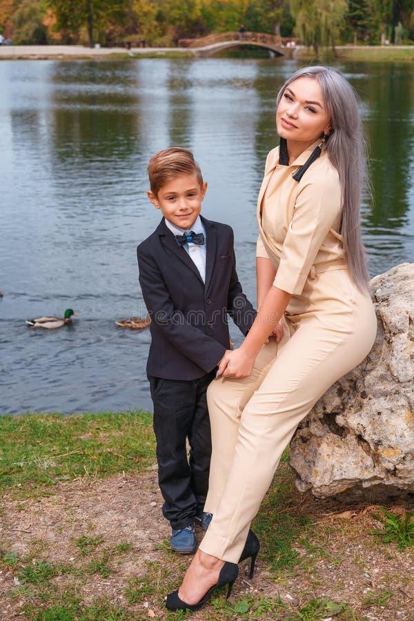 Caminhada da m?e e do filho no parque pelo lago foto de stock