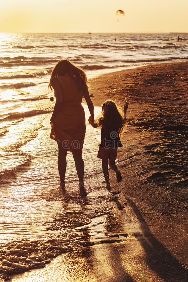 Caminhada da mamã e da filha ao longo da praia no por do sol imagem de stock