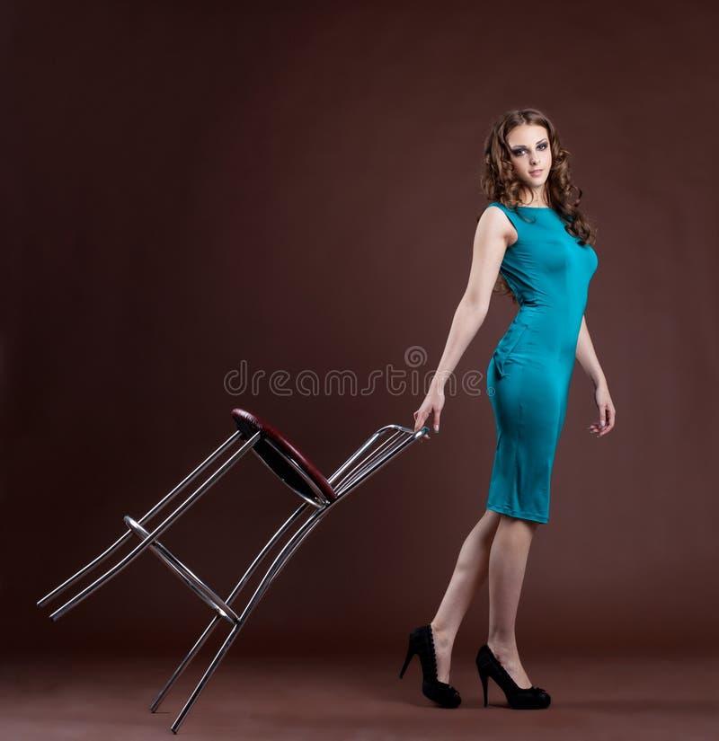 Caminhada da menina da beleza com cadeira da barra imagem de stock