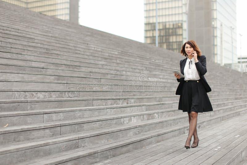 Caminhada da mulher de negócio ao longo do discurso das escadas fotografia de stock