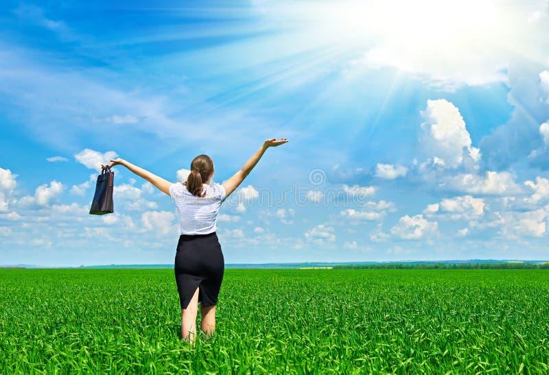A caminhada da mulher de negócio no campo de grama verde exterior e relaxa sob o sol A moça bonita vestiu-se no terno que descans fotografia de stock