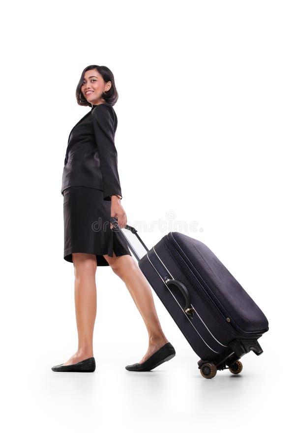 Caminhada da mulher de negócios uma mala de viagem, corpo completo imagem de stock