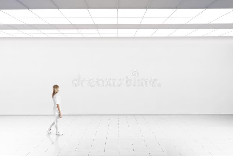 Caminhada da mulher na galeria do museu com parede vazia imagens de stock royalty free